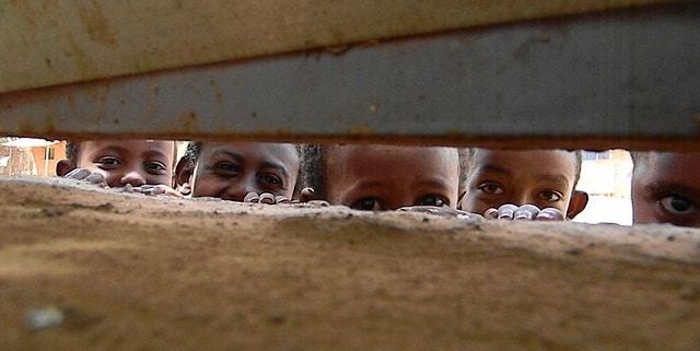 3 ילדים אתיופיים מסתכלים מבעד לחרך