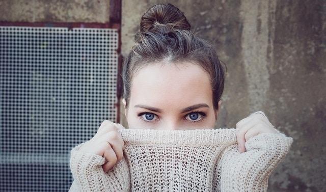 אישה מכסה את הפנים עם סוודר